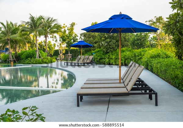 Beautiful luxury umbrella and chair around outdoor swimming pool in hotel