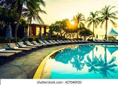 Beautiful luxury umbrella and chair and coconut palm tree around outdoor swimming pool in hotel resort at sunrise time - Vintage filter and boost up color Processing