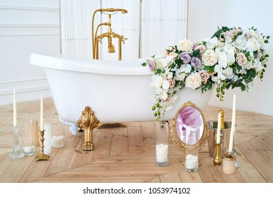 Beautiful luxury vintage empty bathtub with lush floral decorations and candles, mirror on the floor in bathroom interio, copy space. Freestanding white bath with flowers near folding screen