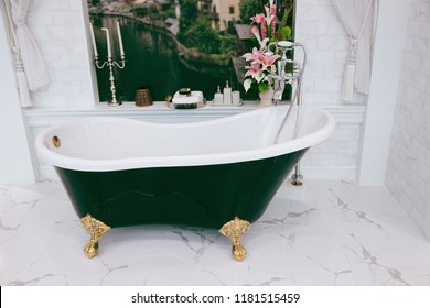Beautiful luxury vintage empty bathtub near big window in bathroom interio, free space. Freestanding white bath. The bathroom is beautifully decorated with marble tiles.