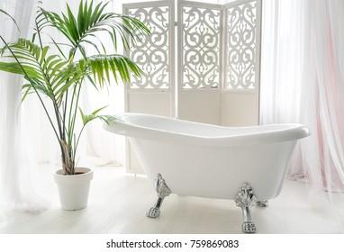 Beautiful luxury vintage empty bathtub near big window in bathroom interio, free space. Freestanding white bath near folding screen and palm tree, copy space
