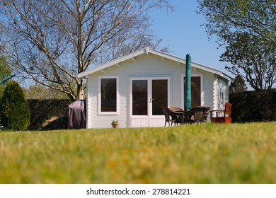 Beautiful luxury wooden Summerhouse in a country garden with tables, chairs, sun umbrella, trees, blue sky, green grass. Summer house is a romantic & relaxing garden retreat.