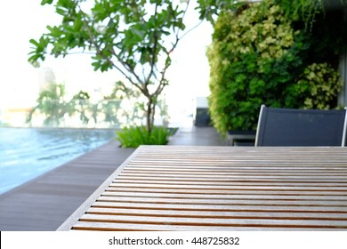 Beautiful luxury wooden table at swimming pool in a condo located on the highest floor