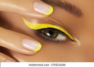 Beautiful macro close-up of female Eye with bright yellow Eyeliner Makeup. Neon Disco make-up and Fashion Manicure. Summer beauty styleCloseup macro shot of fashion liner eyes visage