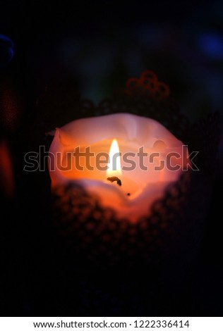 Beautiful macro photo of a small candle with a flame against a dark background