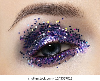 Beautiful macro shot of female eye with ceremonial makeup. Perfect shape of eyebrows, eyeliner and pretty blue sparkle on eyelid. Cosmetics and make-up. Closeup macro shot of fashion sparcle visage