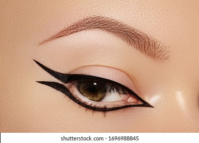 Beautiful macro shot of female eye with fashion black eyeliner makeup. Perfect graphic liner shape, minimalism style visage. Cosmetics and make-up. Closeup macro shot of fashion liner eyes visage