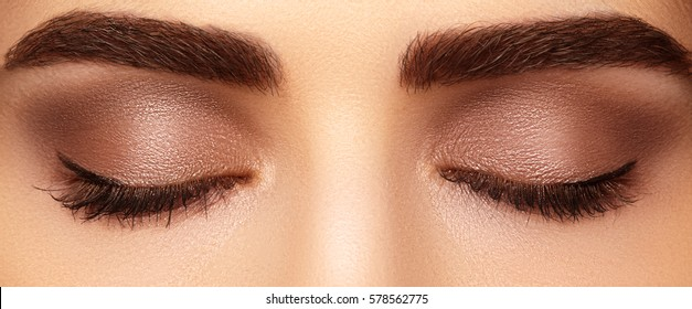 Beautiful macro shot of female eye with classic smoky makeup. Perfect shape of eyebrows, brown eyeshadows and long eyelashes.Closeup macro shot of fashion smoky eyes visage. Before and after