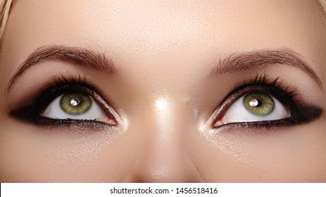 Beautiful Macro Shot of Female Eyes with Fashion Black Smoky Makeup. Cosmetics and Make-up. Dark Eyeshadows on Eyelids. Clean and Soft Skin. Look Up