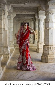 Beautiful Maharani. Young Indian Woman in Red bridal Sari clothing with bridal oriental jewelry. Beautiful Indian Girl in Wedding Sari. Indian Bride in the ancient Jain Temple, Ranakpur. Wedding day