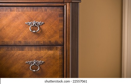 Beautiful mahogany wood cabinet. Detail shot with cream wall and molding in background.