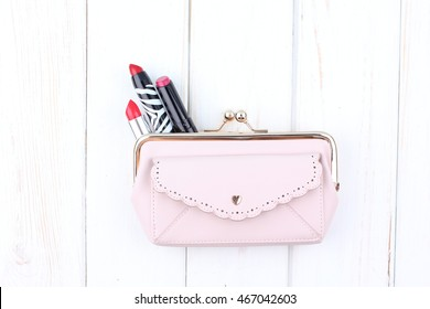 Beautiful make up bag with cosmetics on white wooden background