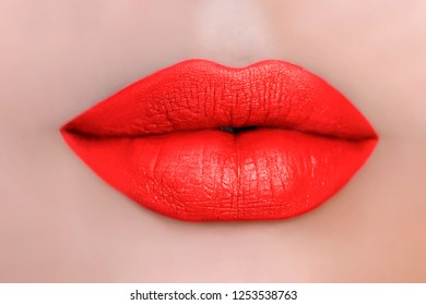 Beautiful make up of glamour coral red lips, lipstick on the face of an attractive beautiful woman as a beauty and health concept pertaining to cosmetics and female business fashion