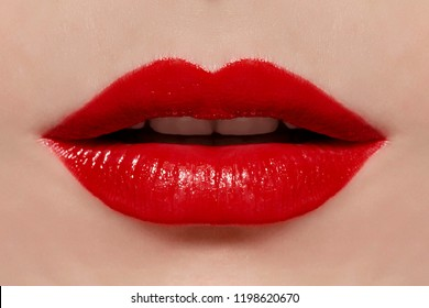 Beautiful make up of glamour red lips, lipstick on the face of an attractive beautiful woman as a beauty and health concept pertaining to cosmetics and female business fashion