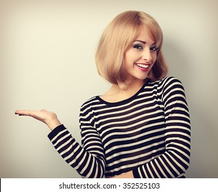 Beautiful makeup blond woman holding and presenting something in the hand. Toned portrait