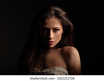 Beautiful makeup seriois woman with long hair looking sexy with half shadow on the face. Closeup portrait. Art