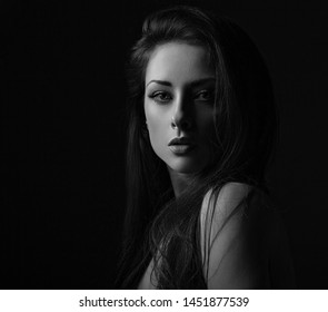 Beautiful makeup seriois woman with long hair looking sexy with half shadow on the face. Closeup portrait. Art. Black and white