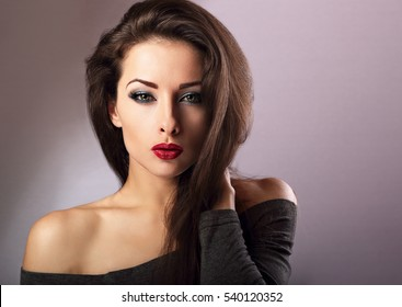 Beautiful makeup sexy woman with hot red lipstick and long eye lashes looking expression on blue background