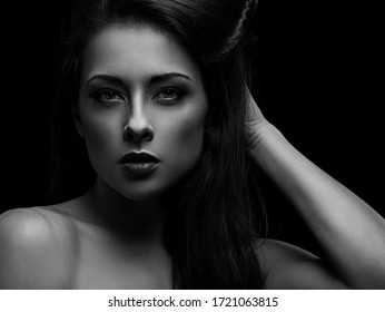 Beautiful makeup sexy woman with long hair looking serious holding long brow hair on black background. Closeup portrait. Art.Expression portrait. Vogue. Black and white