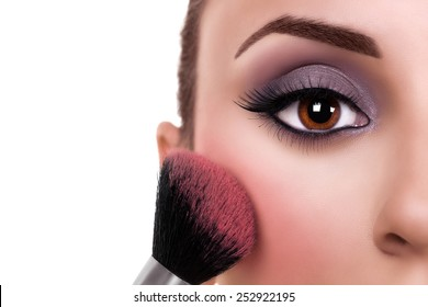 Beautiful makeup woman with make up brush on white with copy space. Blush.