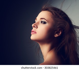 Beautiful makeup woman profile with long hair looking up with hope on light on dark background