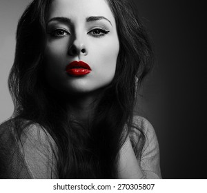 Beautiful makeup woman with red lips looking sexy. Black and white closeup portrait in darkness