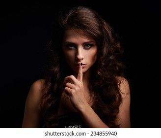 Beautiful make-up woman showing silence sign the finger near lips on black background