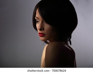 Beautiful makeup woman with thinking sad look and short hair style, red lipstick on dark shadow background. Closeup portrait