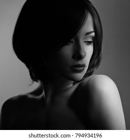 Beautiful makeup woman with thinking sad look and short hair style, red lipstick on dark shadow background. Closeup portrait. Black and white. Art