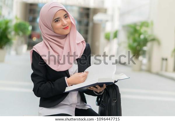 Beautiful Malay girl holding books outdoor