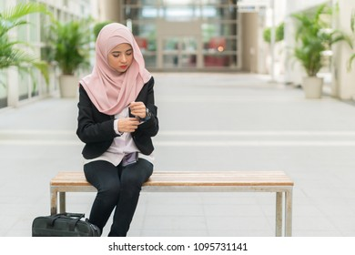 Beautiful Malay girl holding mobile phone outdoor