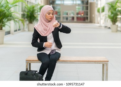 Beautiful Malay girl holding mobile phone outdoor looking at the watch