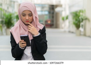 Beautiful Malay girl holding smartphone and thinking outdoor