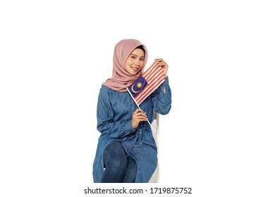 Beautiful Malay girl waving a Malaysian flag celebrating Merdeka Day (Independence Day)
