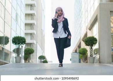 Beautiful Malaysian girl using mobile phone and carrying bag outdoor