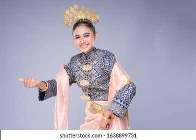 A beautiful Malaysian traditional female dancer with a charming smile performing a cultural dance steps in a traditional outfit. Half length isolated in grey.