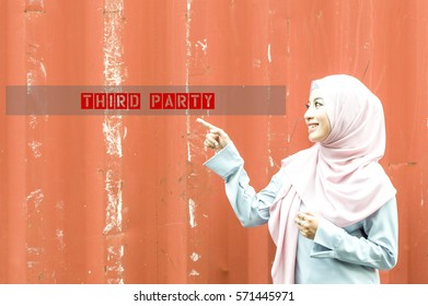 The beautiful Malaysian young lady with muslimah attire  pointing her finger to the words Third Party   . A logistic terms for shipping and forwarding with scratch container background.