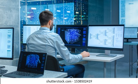 Beautiful Male Computer Engineer and Scientists Create Neural Network at His Workstation. Office is Full of Displays Showing 3D Representations of Neural Networks. - Shutterstock ID 1538502419