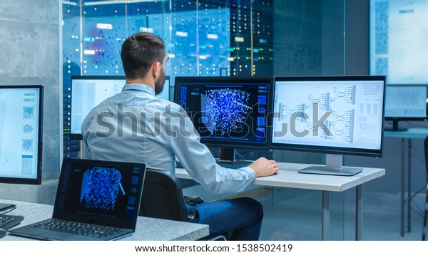 Beautiful Male Computer Engineer and Scientists Create Neural Network at His Workstation. Office is Full of Displays Showing 3D Representations of Neural Networks.