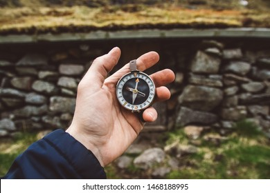 Beautiful male hand holds a magnetic compass against the background of the house and mountains rocks. The concept of finding yourself the way and the truth.