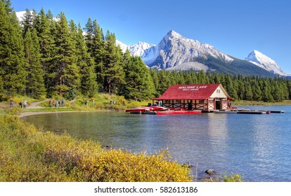 Beautiful Maligne Lake with a boathouse were you can rent canoes and snow covered  mountains at the background
