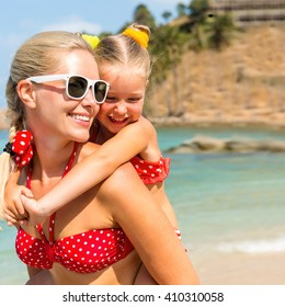 Beautiful mammy sunglasses with cute little daughter on her back. Two in red bikini. Woman smile and little lady hugging her. Happy family on the sea shore. Happy mothers day.