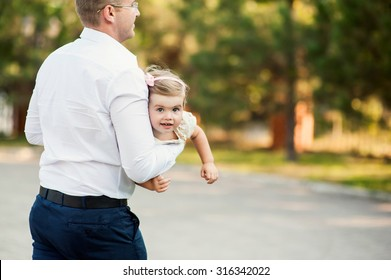 Beautiful man and child have a fun in the park together. A man dressed in a business-like style, using his free time to spend time with his lovely daughter.