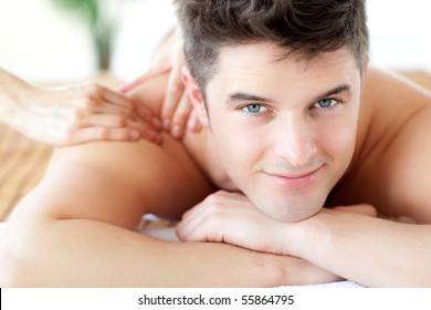 Beautiful man enjoying a back massage in a Spa center