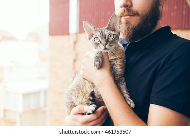 Beautiful man is holding and hugging cute curious Devon Rex cat. Happy young man is standing on a balcony with his cat. Home pets, Lifestyle