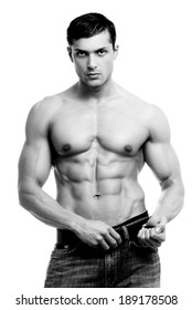 Beautiful man with muscular body holding the belt.