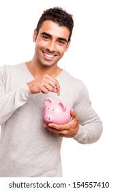 Beautiful man saving money to a piggy bank
