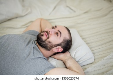 Beautiful man sits in bed and relaxes.