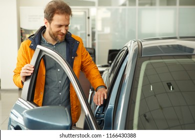 Beautiful man smiling and standing near dark blue automobile in car center and choosing auto. Handsome male customer looking at cars in showroom of modern car dealership.