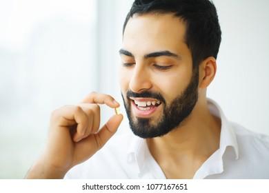 Beautiful Man Taking Pill, Medicine. Vitamins And Supplements
